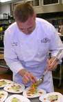 Chef plating red curry salmon.JPG